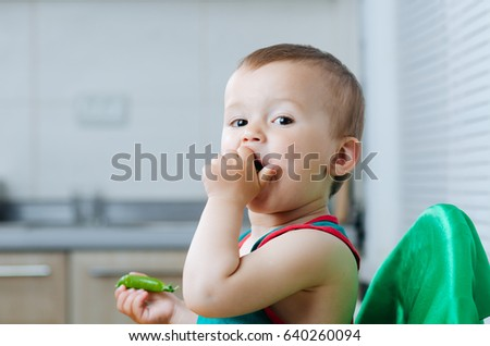 Little, cute Boy cleans and eats the peas in the kitchen