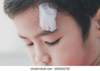 Little cute boy with a cracked head and doctor using gauze closure the wound
