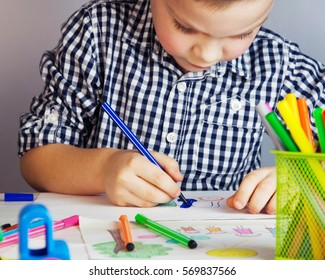 Little cute boy draws with color pencils.