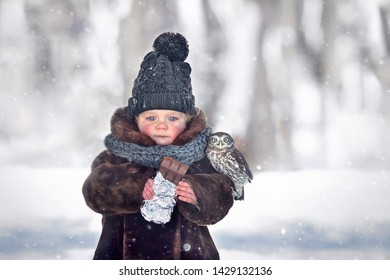 Little cute boy is eating a chocolate with his friend little owl in winter outside in Russia. Image with selective focus and toning.