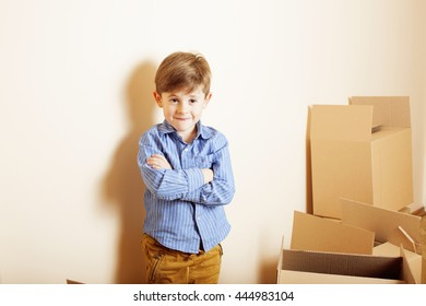 little cute boy in empty room, remoove to new house. home alone emong boxes