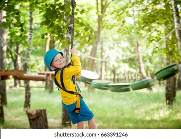 Little cute boy enjoying activity in a climbing adventure park on a summer sunny day. toddler climbing in a rope playground structure. Safe Climbing extreme sport with helmet and Carabiner