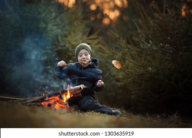 Little cute boy is frying and eating bread on the fire. Image with selective focus and toning.