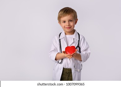 Little, cute boy future doctor dressed white medical apron  with stethoscope  and red heart on white background