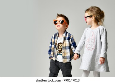 Little cute boy girl hold hands playing on grey background. Happy family close up . brother and sister smiling in pink and orange heart sunglasses