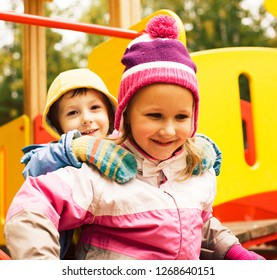 little cute boy and girl playing outside on playground