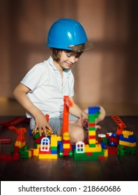 A little cute boy in a hard hat playing with bricks and building a toy city.