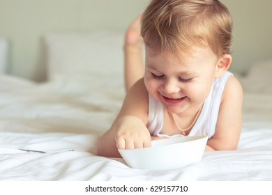 Little cute boy having breakfast in bed. Boy playing in bed. Breakfast in bed.