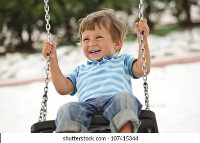 Little cute boy having fun on chain swings.