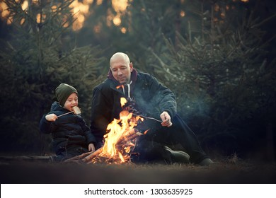 Little cute boy and his father are frying and eating bread on the fire. Image with selective focus and toning.