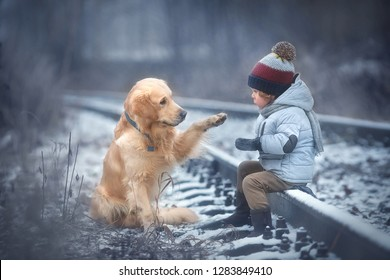 Little cute boy and his friend labrador dog are walking in the winter forest. A dog is asking a bagel! Image with selective focus and toning