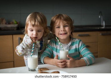 A little cute boy and his little sister  drink milk and eating cookies in kitchen.