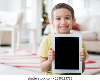 Little cute boy at home holding tablet with copy space