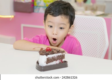 Little cute boy looking at a cake on the table.