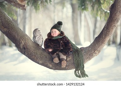 Little cute boy with owl sitting on the curved tree. Image with selective focus and toning.