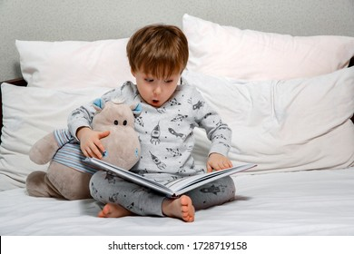 Little cute boy in pajamas reading a toy book sitting on the bed. Bedtime stories before bed.