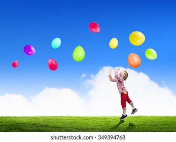 Little cute boy playing joyfully with colorful balloon