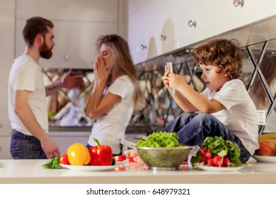 Little cute boy playing phone games while his parents fighting on the background.