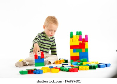 Little cute boy playing with plastic building blocks. Isolated on white.