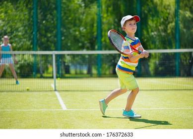 Little cute boy playing tennis on green court
