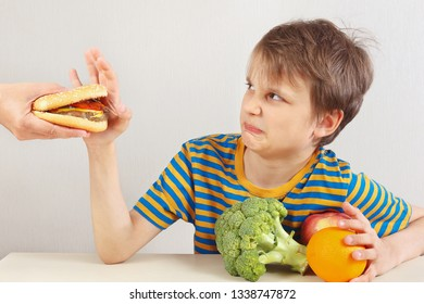 Little cute boy in a striped shirt at the table refuses hamburger in favor of healthy diet on a white background
