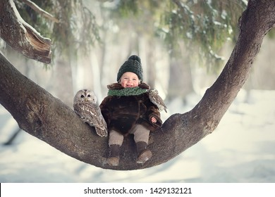 Little cute boy with two owl sitting on the curved tree. Image with selective focus and toning.