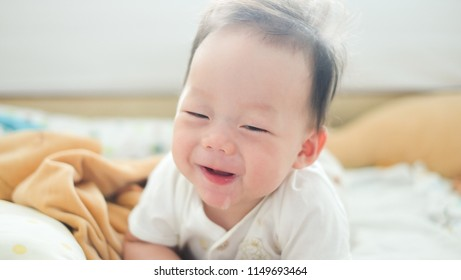 The little cute boy wakes up in the morning with funny smiling.