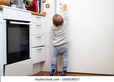 A little cute boy wants to open a door in the room. Portrait of a baby trying to reach a door-handle in the kitchen by his hand. Children security.