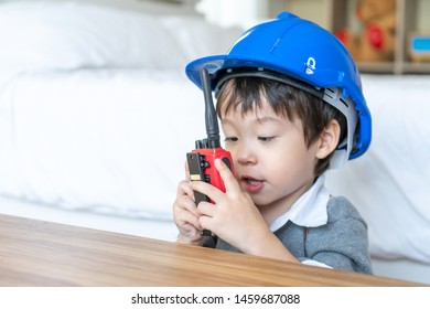 Little cute boy wearing blue helmet and enjoying to talking with red walkie-talkie redio in the bedroom, copy space