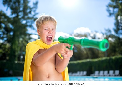 Little cute boy wearing yellow towel  shouting and playing with water gun at swimming pool  on summer day outdoors