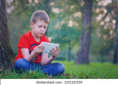 Little cute boy  working and playing on his tablet