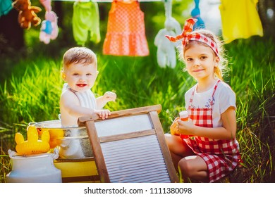 Little cute brother in apron bathing in pelvis and pretty sister in checkered dress headband laughing sitting together outdoors