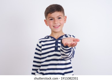 little cute Caucasian boy kid wearing stripped t-shirt against white wall smiling friendly offering something with open hand or handshake as greeting and welcoming. Successful business.