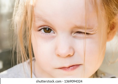 Little cute Caucasian girl with brown eyes squints in the sun, winks and makes a face. Large portrait, the eyes of a child in soft focus