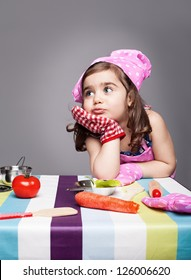 little cute chef thinking about the meal she wants to prepare on grey background