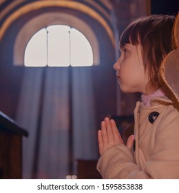 Little cute child girl prayingagainst bloor background of church. Faith, religion, prayer concept.