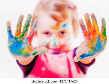 Little cute child girl showing painted hands. Education, school, art and painting concept.