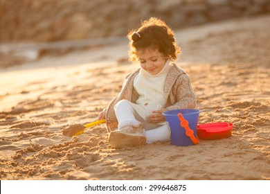Little cute child girl sitting on sand and playing with toys, outdoor