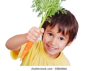 A little cute child holding a fresh carrot in hand