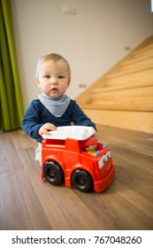 Little cute child playing with many kinds of toys on the wood floor in the modern apartment, looking happy and satisfying