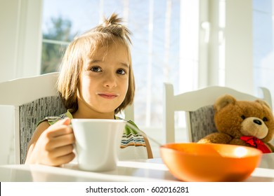 Little cute child playing with Teddy bear at home having fun and happiness