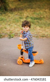 Little cute child riding orange scooter in city street. Beautiful small toddler boy playing active games outdoors on warm summer or autumn day. Vertical color photo.