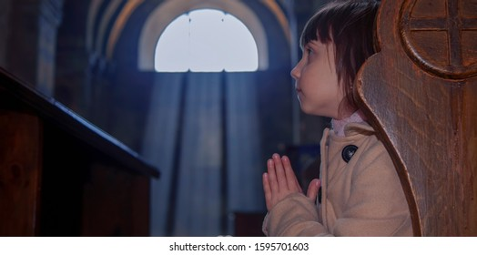 Little cute Christian child girl praying against the background of the window and the rays of the sun in the church. Faith, religion, prayer concept.