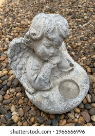 Little cute cupid angel sculpture on river gravel background in the english  garden.