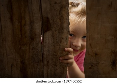 Little cute curious smiling child peering over the wooden fence close up. Hide-and-seek game.
