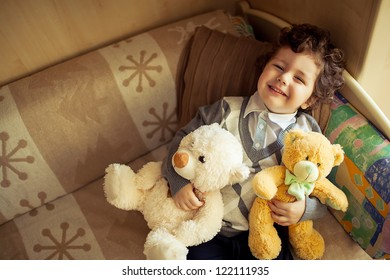 little cute curly  boy laying at couch with teddy bear,top view