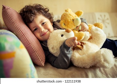 little cute curly  boy laying at couch with teddy bear