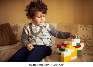 little cute curly  boy sitting at couch with constructor