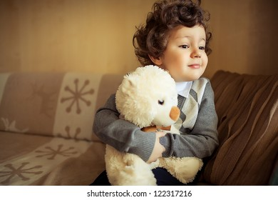 little cute curly  boy sitting at couch with teddy bear