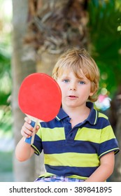 Little cute funny kid boy with table tennis racquet playing in domestic garden. Active outdoors games and leisure for children lifestyle.